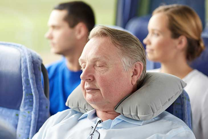 Senior man sleeping in travel bus with neck pillow